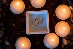 Hochzeitsdiamantring mit Kerzen im Wasser stockfotografie