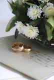 Hochzeitseinladung, goldene Ringe und Blumen Stockfotografie