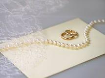 Hochzeitseinladung mit einer Perlenhalskette und goldenen Ringen Stockbild