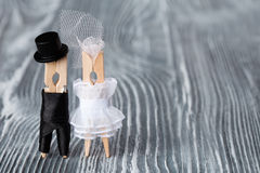 Hochzeitseinladungs-Kartenschablone Wäscheklammern pflegen sich im schwarzen weißen Kleid des Anzugs und der Braut auf grauem höl Stockbilder