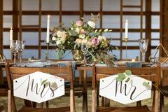 Hochzeitsfest Viele Weingläser auf grüner Tabelle Kerzen und Blumenstrauß Abbildung der roten Lilie Lizenzfreies Stockbild