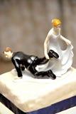 Hochzeitsfigürchen mit der Braut, die den Bräutigam schleppt Lizenzfreies Stockbild