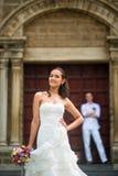 Hochzeitsfoto mit Braut und Bräutigam Die schöne aufwerfende Braut und hinter ihr ist der Bräutigam nahe der katholischen Kirche lizenzfreie stockbilder