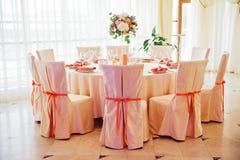 Hochzeitsgasttabelle verziert mit Blumenstrauß und Stühlen mit Bögen Stockbilder