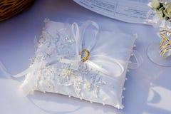 Hochzeitsgoldringe auf weißem Kissen Lizenzfreies Stockfoto