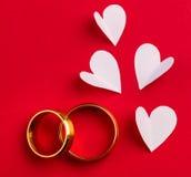 Hochzeitshintergrund - zwei Goldeheringe und handgemachte Herzen Lizenzfreie Stockbilder