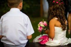 Hochzeitskinder mit rosafarbenem Blumenstrauß Stockfotografie