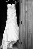 Hochzeitskleid, das in einem Eingang hängt Lizenzfreie Stockfotos