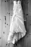 Hochzeitskleid, das an einer Täfelungswand hängt Stockbilder