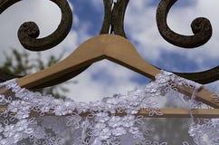 Hochzeitskleid - Hochzeitskleid, das am Haken mit Hintergrundschmiedeeisen des blauen Himmels hängt lizenzfreie stockbilder