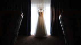 Hochzeitskleid, das vor dem Fenster hängt stock footage