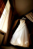 Hochzeitskleid in der schönen Leuchte im noblen Raum Stockfotografie