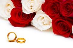 Hochzeitskonzept - Rosen und Ringe Stockfoto