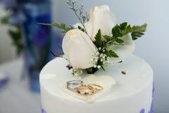 Hochzeitskuchen und -deckel mit Hochzeitsringen stockfotos