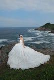 Hochzeitsmädchen an der Klippe Stockfotografie