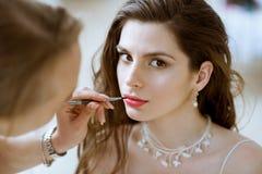Hochzeitsmaskenbildner, der eine Wieder gutmachung Braut macht lizenzfreie stockfotografie