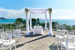 Hochzeitsorteinstellung, -bogen und -altar verziert mit Rosen, Blumen, Ozeanhintergrund Stockfoto