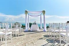 Hochzeitsorteinstellung, -bogen und -altar verziert mit Rosen, Blumen, Ozeanhintergrund Stockfotografie