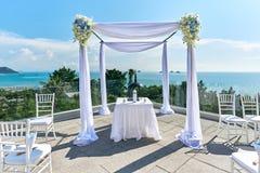 Hochzeitsorteinstellung, -bogen und -altar verziert mit Rosen, Blumen, Ozeanhintergrund Stockfotos