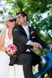 Hochzeitspaare auf einem Motorrad Stockbild