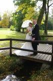 Hochzeitspaare auf hölzerner Brücke im Herbst Lizenzfreies Stockfoto