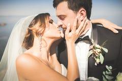 Hochzeitspaare, Bräutigam, Braut mit dem Blumenstrauß, der nahe Meer aufwirft und blauer Himmel lizenzfreies stockbild