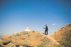 Hochzeitspaare, Bräutigam, Braut mit dem Blumenstrauß, der nahe Meer aufwirft und blauer Himmel stockfotografie