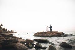 Hochzeitspaare, Br?utigam, Braut mit dem Blumenstrau?, der nahe Meer aufwirft und blauer Himmel stockbilder