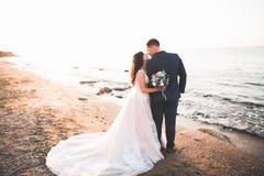 Hochzeitspaare, Br?utigam, Braut mit dem Blumenstrau?, der nahe Meer aufwirft und blauer Himmel stockbild