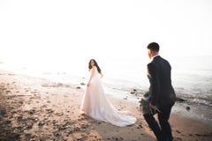 Hochzeitspaare, Br?utigam, Braut mit dem Blumenstrau?, der nahe Meer aufwirft und blauer Himmel lizenzfreies stockfoto