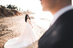 Hochzeitspaare, Br?utigam, Braut mit dem Blumenstrau?, der nahe Meer aufwirft und blauer Himmel stockfotos