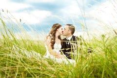 Hochzeitspaare, -braut und -bräutigam, die im Gras küssen Lizenzfreie Stockfotografie