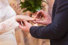Hochzeitspaare - Braut und Bräutigam - tragende Eheringe miteinander Stockfotografie