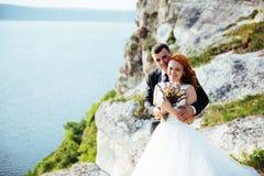 Hochzeitspaare, die über schöner Landschaft bleiben lizenzfreies stockfoto