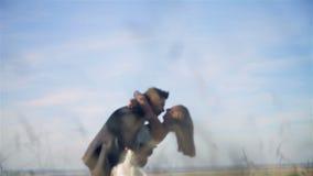 Hochzeitspaare, die auf dem Gebiet küssen stock video footage