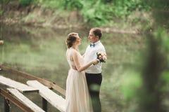 Hochzeitspaare, die an der Brücke umarmen und küssen stockfoto