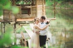 Hochzeitspaare, die an der Brücke umarmen und küssen lizenzfreies stockfoto