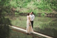 Hochzeitspaare, die an der Brücke umarmen und küssen stockfotografie