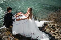 Hochzeitspaare, die an der Verzierung sitzen und umarmen stockfotografie