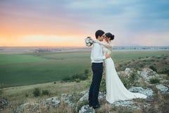 Hochzeitspaare, die im Gebirgshügel auf Sonnenuntergang schauen Lizenzfreie Stockfotografie