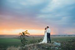 Hochzeitspaare, die im Gebirgshügel auf Sonnenuntergang schauen Lizenzfreie Stockfotos