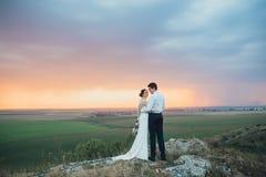Hochzeitspaare, die im Gebirgshügel auf Sonnenuntergang schauen Lizenzfreies Stockfoto