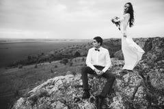 Hochzeitspaare, die im Gebirgshügel auf Sonnenuntergang schauen Stockfoto