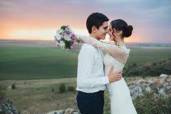 Hochzeitspaare, die im Gebirgshügel auf Sonnenuntergang schauen Lizenzfreies Stockbild