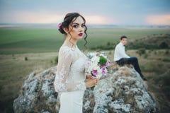 Hochzeitspaare, die im Gebirgshügel auf Sonnenuntergang schauen Stockfotografie