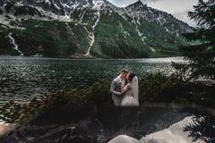 Hochzeitspaare, die nahe dem See in Tatra-Bergen in Polen k?ssen Morskie Oko Sch?ner Sommer-Tag lizenzfreies stockfoto