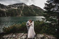 Hochzeitspaare, die nahe dem See in Tatra-Bergen in Polen k?ssen Morskie Oko Sch?ner Sommer-Tag lizenzfreie stockbilder