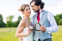 Hochzeitspaare, die Pferdeschuh zeigen Stockfoto