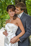 Hochzeitspaare, die unter verdrehten Buschniederlassungen umfassen Stockfotografie
