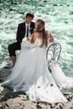 Hochzeitspaare, die am verzierten Tisch sitzen und Th feiern stockbild